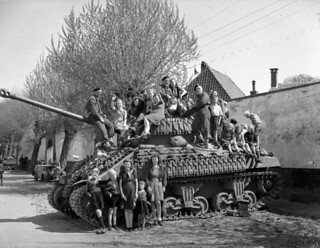 Dutch women and children sitting on a Sherman VC Firefly tank of Lord Strathcona's Horse (Royal Canadians) / Des femmes et des enfants hollandais assis sur un char Sherman VC Firefly du régiment Lord Strathcona's Horse (Royal Canadians)