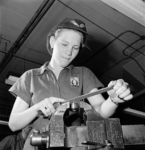 Woman factory worker files a machine part while piped music plays on loudspeakers.  / Une ouvrière d'usine lime une pièce de machine pendant que des hauts-parleurs diffusent de la musique