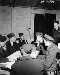 Debriefing of aircrew of No. 433 Squadron, RCAF, after a raid on German flying-bomb sites in France, 1944 / Débriefing de l'équipage du 433e Escadron de l'ARC après un raid sur des rampes de lancement de bombes volantes en France, 1944