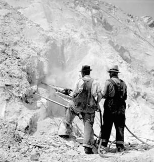 Workmen drilling holes for blasting asbestos ore in the Bell Company's open-pit mine, Thetford-Mines, Que., 1944 / Ouvriers perçant des trous pour le dynamitage dans la carrière d'amiante à ciel ouvert de la Bell Company, Thetford-Mines, Qc, 1944