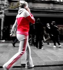 Women in track suit walking while talking on a mobile phone