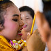 Teenage girl looking at her new teeth in a mirror during the the tooth filing ceremony, Bali island, Canggu, Indonesia