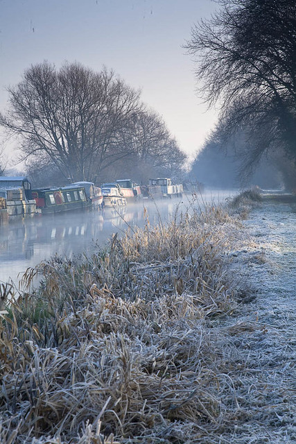 Barges moored along the banks of the River Kennet at Burghfield near Reading, Berkshire early on a cold and frosty winter's morning