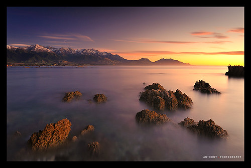 ocean longexposure blue red sea newzealand orange snow mountains sunrise rocks pacificocean southisland seawardkaikourarange