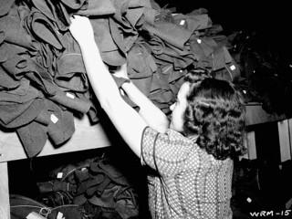 Woman sorts out Army uniforms for shipment to Army stores. / Une femme trie des uniformes militaires destinés aux entrepôts de l'armée