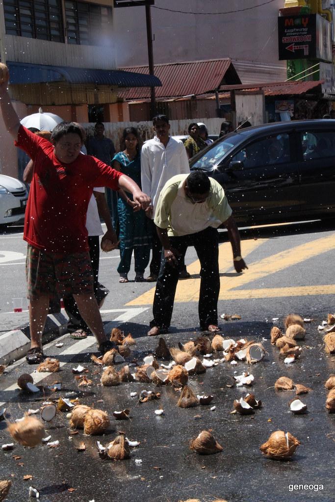 Devotees smashing coconuts