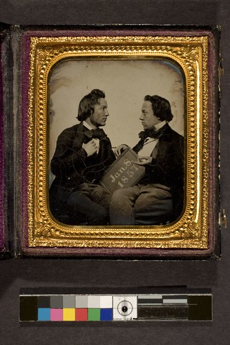 portrait of two men holding slate, upon which is written the date, Jan. 8, 1857