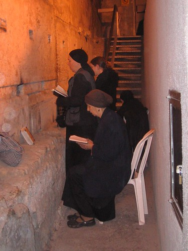 Women pray opposite the longest stone