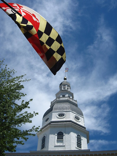 State House dome with flag in foreground
