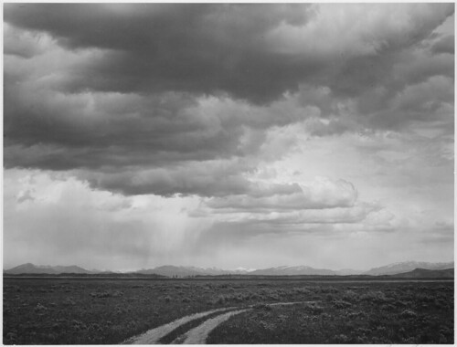 "Roadway, low horizon, mountains, clouded sky, ""Near (Grand) Teton National Park."""