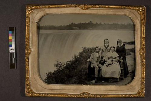 Four people seated near Horseshoe Falls, Table Rock, Niagara Falls