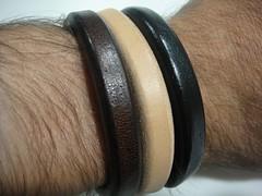 hand(0.0), arm(0.0), leather(0.0), jewellery(0.0), ear(0.0), gadget(0.0), audio equipment(0.0), headphones(0.0), brown(1.0), bangle(1.0), bracelet(1.0),