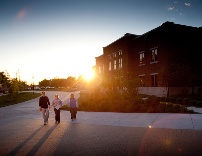 Newman students walking through Founders' Plaza at sunset