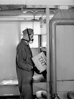Workman wearing protective face mask loads case of T.N.T. into machine at the Cherrier bomb-making plant. / Un ouvrier portant un masque de protection charge une caisse de T.N.T. dans une machine à l'usine de fabrication de bombes Cherrier