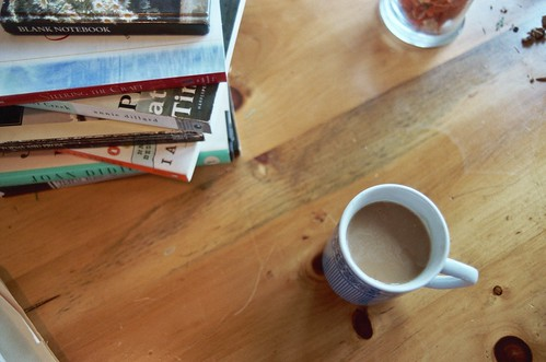 coffee and pile of books: kitchen table mfa