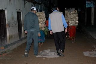 Two Tibetan men praying while walking down the street, with women porters carrying large bundles of wood on their back, night, Boudha, Kathmandu, Nepal