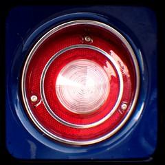 window(0.0), symbol(0.0), wheel(0.0), rim(0.0), glass(0.0), headlamp(0.0), emblem(0.0), lighting(0.0), spoke(0.0), automotive tail & brake light(1.0), automotive lighting(1.0), red(1.0), light(1.0), circle(1.0),