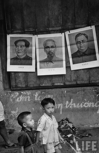 Children playing under posters displaying Communist leaders. Hanoi 1954