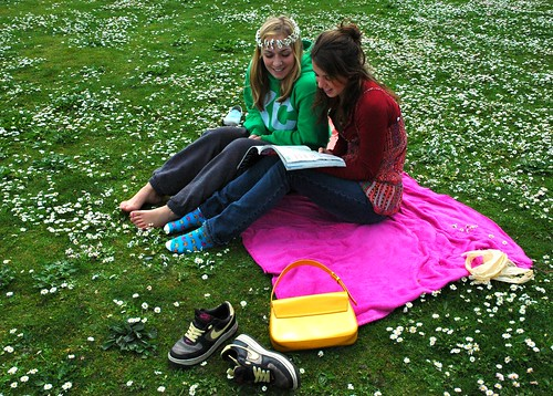 On a pink, green, and white cloud, two young women reading a book at Greenlake, with a daisy chain in a field of flowers, Seattle, Washington, USA