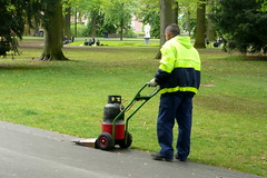 asphalt(1.0), outdoor power equipment(1.0), vehicle(1.0), lawn mower(1.0), lawn(1.0),