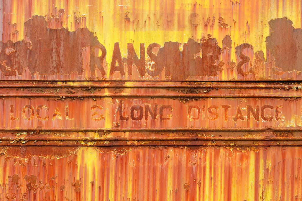 Fading paint on a rusty old moving van says 'Local & Long Distance'