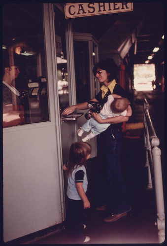Mother with Her Children at the Cashier's Window Paying for Her Annual Sticker after Her Car Had Successfully Passed Testing at an Auto Emission Inspection Station in Downtown Cincinnati, Ohio...09/1975
