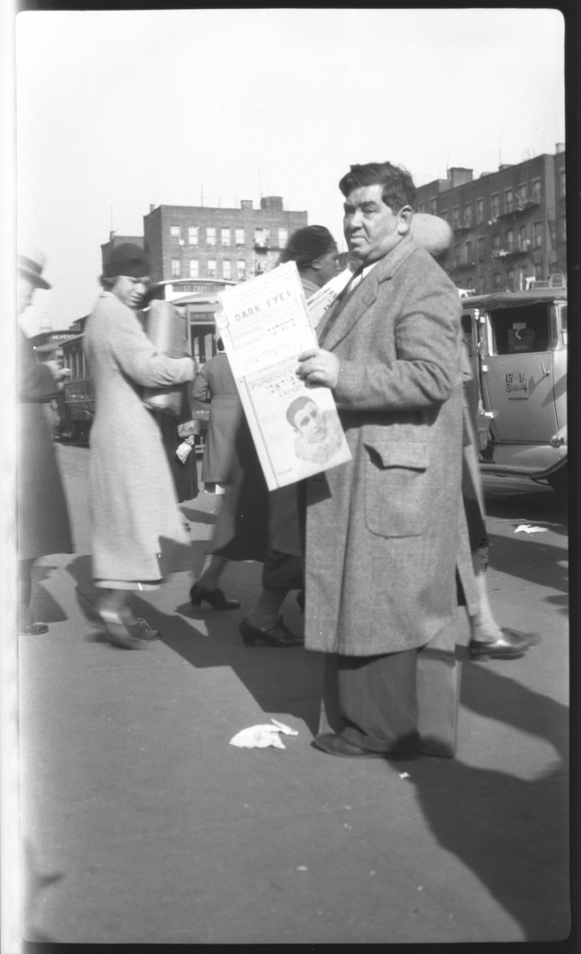Man selling Yiddish song sheets at Northeast corner of Essex and Delancey Streets, New York.