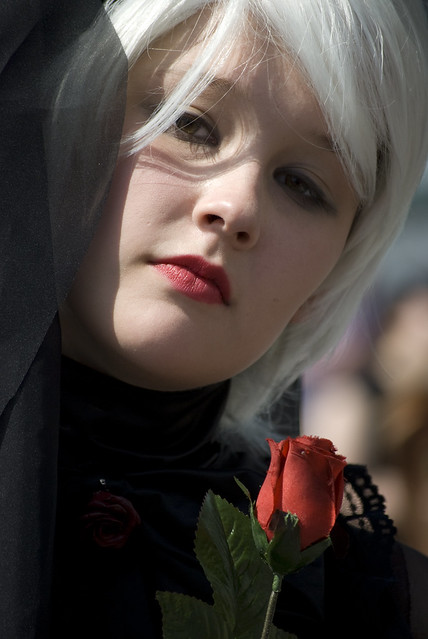 Black clad, white haired cosplay girl with a red rose