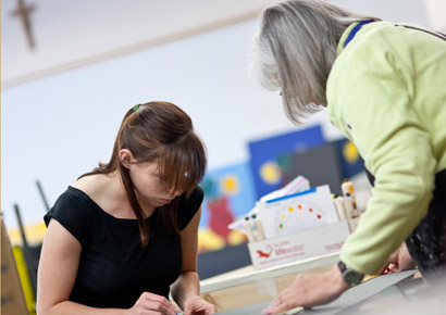 Director of Visual Arts Mary Werner helps a Newman student during art class