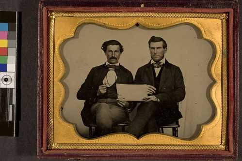 portrait of two men with tuning fork and sheet of paper in hand