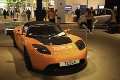automobile(1.0), tesla(1.0), exhibition(1.0), tesla roadster(1.0), vehicle(1.0), automotive design(1.0), auto show(1.0), land vehicle(1.0), supercar(1.0), sports car(1.0),