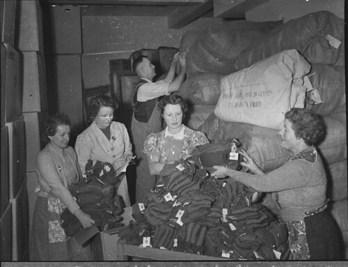 Women volunteer workers doing up clothing parcels at the ACF rooms (taken for Australian Comforts Fund), Sydney, 1944 / photographer Sam Hood