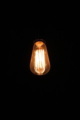 chandelier(0.0), lantern(0.0), lamp(1.0), incandescent light bulb(1.0), light fixture(1.0), yellow(1.0), light(1.0), darkness(1.0), lighting(1.0),