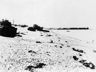 Canadian dead litter the Dieppe beach among ruined and abandoned tanks. / Les corps de soldats canadiens sur la plage de Dieppe entouré par des chars d'assaut abandonnés et détruits
