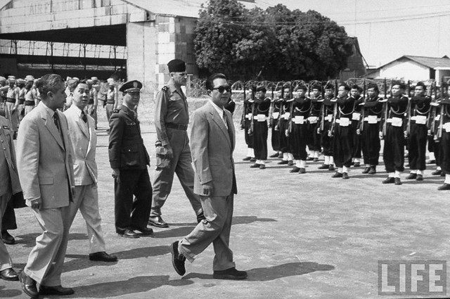 March 1954 - Emperor, Bao Dai, nattily attired in well-tailored suit, sun glasses, sport shoes, and tailed by Gen. Rene Cogny (C) and Indo-Chinese officials
