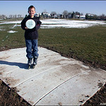 Kyle Panis shows off his new disc on the new tee pad on hole #1 at Aurora Expo Park