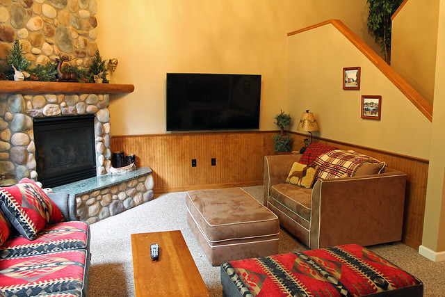 The great room in Morning Moose features a floor to ceiling stone fireplace; flat screened TV; open stairway;  picture windows overlooking a private back yard/outdoor living area;