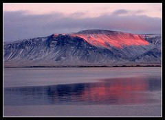 The last rays of the setting sun color Mount Esja on a cold winter day