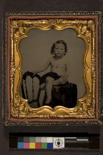 Portrait of nude child seated on posing table