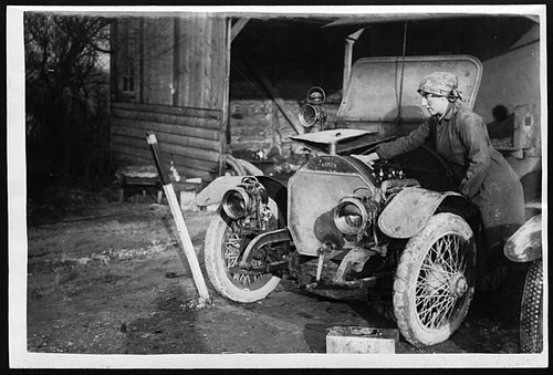 A young woman, a member of the First Aid Nursing Yeomanry, oils her car engine, ina black and white image from early 20th century