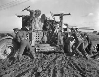 Gunners of the 2nd Heavy Anti-Aircraft Regiment, RCA, pushing a 3.7-inch anti-aircraft gun through mud, 1945 / Artilleurs du 2e Régiment d'artillerie antiaérienne lourde, RCA, qui poussent un canon antiaérien de 3,7 pouces dans la boue, 1945