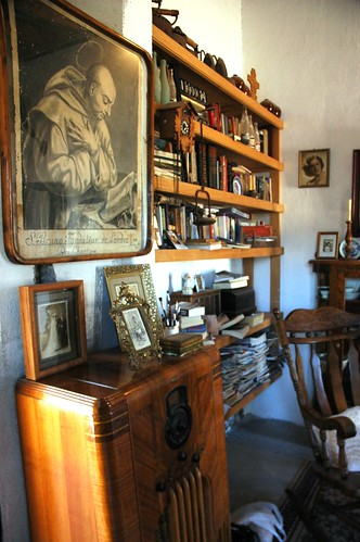 Portrait of San Bruno (Saint Bruno), with Beto Romano's family portraits, 1930's radio, Cross, book case, books and papers, rocking chair, Serena Hotel, San Bruno, Baja California Sur, Mexico by Wonderlane
