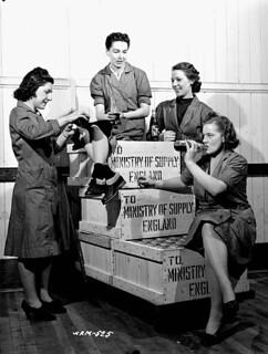 Female workers taking a break from packing crates of 25-pounder field gun cases at a munitions plant / Ouvrières chargées de remplir des caisses de douilles d'obus pour canons de 25 lb, dans une fabrique de munitions, prenant une pause