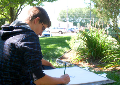 Newman University student drawing during art class