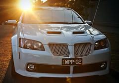 automobile(1.0), automotive exterior(1.0), vehicle(1.0), compact car(1.0), bumper(1.0), pontiac g8(1.0), land vehicle(1.0), vehicle registration plate(1.0),