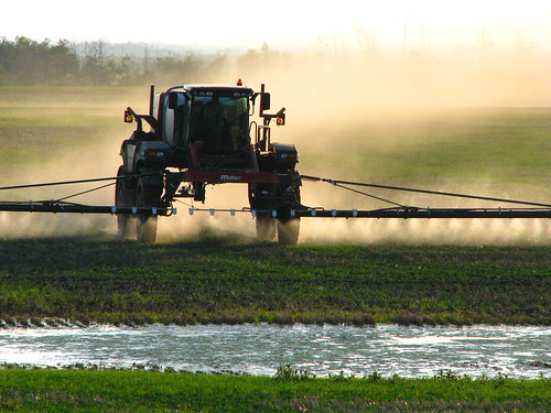 Spraying crops in the evening dusk