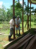 Farmer Rafael Monge and a neighbor cut lumber for the enclosure