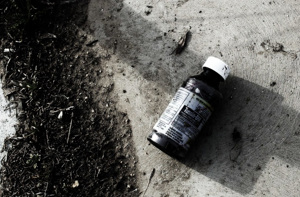 Photograph of a dirt-caked bottle of Tussin DM cough syrup lying in a filthy ditch