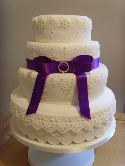 A four tier ivory wedding cake decorated in Broderie Anglaise style