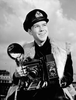 Lieutenant John D. Mahoney of the Royal Canadian Navy Volunteer Reserve, holding an Anniversary Speed Graphic camera. / Le lieutenant John D. Mahoney, de la Réserve des Volontaires de la Marine royale du Canada, tient un appareil-photo Anniversary Speed G